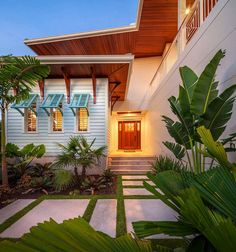 ENTRANCE/exterior: Island modern Large concrete slabs carve out a walkway to this stunning Florida home. Exterior design elements like rich wood soffits and decorative wood brackets pair with tropical landscaping to give the home an island-inspired look. Bermuda Shutters, Bahama Shutters, Blue Shutters, Window Shutters, Window Awnings, Coastal Cottage, Coastal Homes, Veranda Design, Modern Front Yard