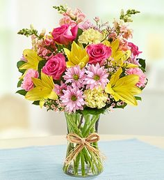 Our bestselling Fields of Europe bouquet is decked out for spring with a mixture of beautiful and bright flowers featuring pink roses, yellow lilies, and many more spring flowers, designed in a glass vase and tied with raffia.