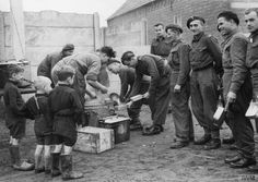 Soldiers of the 1st Polish Armoured Division sharing their rations with Dutch children somewhere on the Tilburg front, Holland, 30 October 1944.