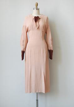 Dusty rose pink 1930s dress with Bishop sleeves decorated with dark burgundy embroidery detail that is echoed in the self-tie ascot tie on the neckline. Dress is cut on the bias and will gracefully hug your curves. Darted bust. No closures, slips overhead. Fabric has some stretch and give.