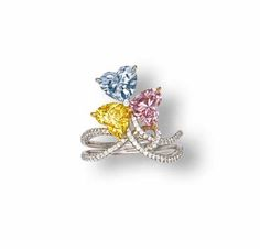A COLOURED DIAMOND AND DIAMOND RING. Set with heart-shaped fancy intense blue, fancy vivid yellow and fancy intense purplish pink diamonds weighing 1.06, 0.91 and 0.88 carats to the diamond bifurcated shoulders, mounted in 18k white, pink and yellow gold.