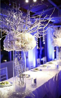 Winter centerpiece, snow and icicles with winter white flowers. Could use a feather white piece in place of flowers. @}-,-;—