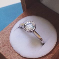 This Brilliant Earth ring features a gorgeous center diamond bezel set and slightly lofted within an intricate halo for a brilliant sparkle.