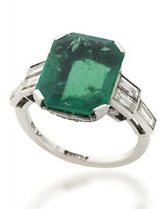 AN ART DECO EMERALD RING. The rectangular cut-cornered emerald to the pierced single-cut diamond-set gallery and three-stone baguette-cut diamond shoulders, raised on a plain hoop, circa 1935.
