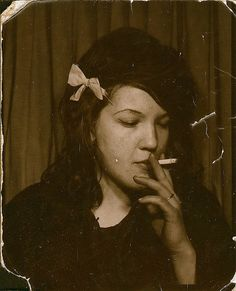 1964 Photo-booth picture. I think we can safely say that this girl is 'trouble'. Dark, badly applied makeup, backcombed hair that isn't well fashioned, and a cigarette.