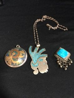 ETHNIC LOT OF JEWELRY INCLUDES A TAXCO MEXICO STERLING PENDANT WITH COPPER, BRASS AND STONE INLAY. ALSO INCLUDED IS A TURQUOISE INLAY ALPACA SILVER MASK PENDANT WITH 20 INCH CHAIN AND THIRD PENDANT WITH SILVER DROPS.