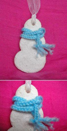 Decorazione a forma di pupazzo di neve: base in pasta di sale verniciata con neve spray; sciarpa realizzata intrecciando fili di lana