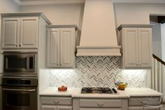 Kitchen Remodel - gray & white herringbone backsplash with painted cabinets and stainless steel appliances