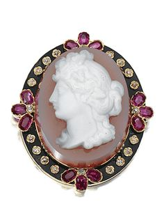 GEM-SET AND CAMEO BROOCH 19TH CENTURY  centring on a carved agate cameo of Flora, the frame decorated with black enamel, set with oval rubies and circular-cut diamonds, circa 1860, later brooch fitting.