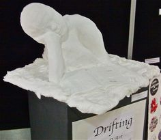 Drifting... Student self portrait posed with a book in the clouds Plastercraft sculpture
