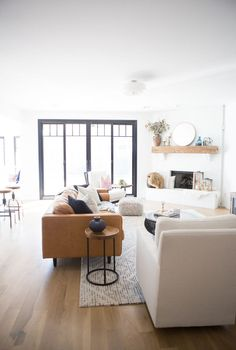 Tulsa Remodel Reveal Modern White Farmhouse black windows and doors modern leather sofa article Sven sofa white brick fireplace wood beam mantle round gold mirror tv gallery wall-1-2