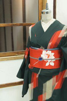 黒の地にパウダーグレーと赤で織り出されたダイヤモンドを重ねたような幾何学デザインがモダンでスタイリッシュな正絹御召の単着物です。