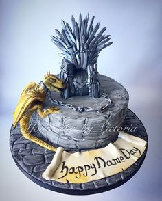 Game of thrones cake! Hand sculpted stone effect on the board and cake painted with a mixture of alcohol and black food colouring to add more depth and shade. Hand made throne using flower paste for the swords, finished in a dark silver and black lustre. Finished with a handmade and edible dragon.