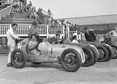 Kay Petre at the wheel of an Austin 7 works team car at Brooklands in 1937, with works team drivers Bert Hadley and Charles Goodacre in the background.  Photo by legendary motorsports photographer and artist Bill Brunell, whose daughter Kitty was also a notable racer.