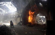 A woman walks past a burning shop in the Maskuf market in the Old City of Homs on May 12, 2014. Syrians streamed back into the ruins of the Old City of Homs on May 10, picking through the remains of their homes and trying to come to terms with the destruction after rebel forces in the Old City were besieged for nearly two years.