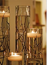 fill glass cylindrical vases with water, put a few twigs at the bottom and float tea candles on top
