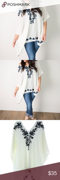 """Embroidered Boho Poncho This boho poncho is the perfect transitional piece to add to your wardrobe. Wear this as a casual bohemian poncho, or as a swimsuit cover up on that cruise you've been saving up for. Off-white, lightweight poncho with navy flower embroidery around the neckline & bottom edge. Measurements:70"""" wide x 28"""" long. 100% viscose. One size fits most, approx 0-14. MODEL is 5'7"""" Tops Tunics"""