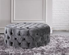 This round footstool is designed with buttoned dimples around the whole item. It is shown in fabric but is also available in leather.