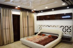 The modern bedroom flaunts a coordinated jali headboard and a ceiling jali pattern, complimented with readymade leather cot in bangalore by A.J Architects. Modern Bedroom, Master Bedroom, Luxury Interior, Interior Design, Common Area, Large Windows, Teak Wood, Luxurious Bedrooms, Cot