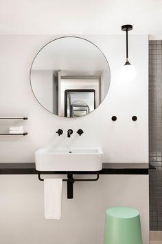 Bathroom with round mirror & black tap wear