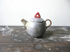 Shino works her magic again with these two teapots.Delight, whimsy, and a cup of tea.Handmade,each piece uniqueApprox 110mm h x 150mm wide (inc handle and spout)1-2 teacupsGrey w/ red triangle top AVAILABLEWhite w/ pink handle SOLD OUTShino TakedaBrooklyn, NY Shino grew up on Kyushu island in southern Japan.Kyushu has a rich history of ceramic