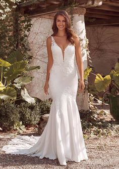 Feel glamorous in this gorgeous crepe fit and flare gown. Embroidered and Venice lace with hand beaded appliqués accentuate your figure. With a deep plunge and illusion back. Finished with a shaped illusion train for stunning wedding pictures. A raised neckline version is available and also an ivory beaded version without silver beading is available.