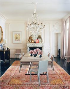 A vibrantly colored oriental rug with red, gold, blue and white is the star if this contemporary dining room. While the grey dining table and chairs are contemporary, every other element in this dining room is traditional- the architectural moldings, chandelier, fireplace and the commode.