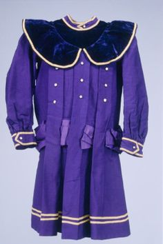1875 Boy's silk, satin, and velvet dress, made of a purple-blue wool twill, with wide matching velvet collar and off-white satin ribbon. The low, loose waistline would help provide a measure of comfort to young children.