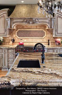 Love the range hood, light glazed cabinets with black island, chandelier.