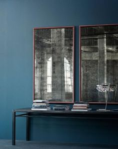 Modern smoky mirrors against a denim-colored wall.