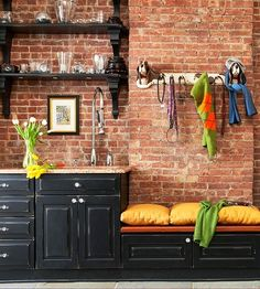 Distressed black cabinets set against a brick wall.