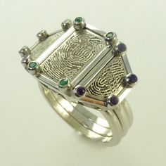 "Platinum triple dress ring with ""fingerprint"" design, set with emeralds and amethysts"