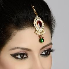 Zircon diamond and pearl studded tikka is a traditional tikka which gives you an alluring look. The tikka is garnished with red stone in the center which is surrounded with zircon diamonds and pearls in the below. The tikka is finished with green hanging droplet and attached with chain. #IndianTraditionalHeadTikka