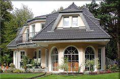 Ein Winkel-Haus als Walmdach-Haus in bayerischen Landhaus-Stil mit Holz-Wintergarten und Halbturm über dem Balkon.