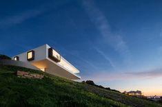 Fotos, planos de planta y secciones de una vivienda construida en una ladera próxima al mar (Algarve). Con patio y deferentes terrazas. Piscina desbordante.