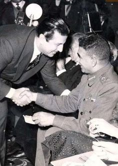 Actor Anwar wagdi shakes Mohamed Naguib's (Egypt's first president) hand.