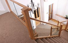Solid oak newel posts and rails with 10mm toughened embedded glass, strings and aprons clad in 6mm oak veneer, plus feature oak curtail step, £7,800, Abbott Wade
