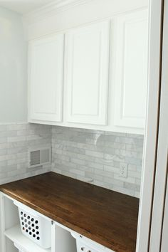 2 x 8 subway bricklay backsplash, white cupboards and butcher's block counter top for kitchen
