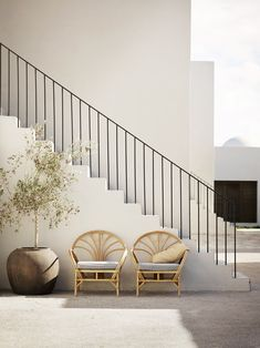 sweet rattan chairs instead of a bench at stair landing - super chic stair and rails too