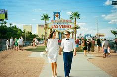 Couple walking towards photographer with Welcome to Las Vegas sign in the background