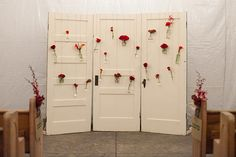 Love the pop of color these scarlet flowers give on this vintage door wedding  backdrop!  Wedding ideas.  wedding decor.  vintage wedding.  rustic wedding. doors.  repurposed doors. vintage doors.  old doors.