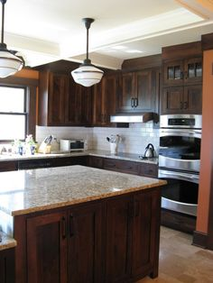 i typically love antiqued cabinets but i love this dark wood. and i love the backsplash!    backsplash ideas for white cabinets | Kitchen Cabinets with white backsplash | home ideas