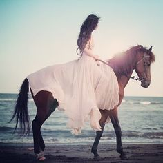 Fairytale portrait of a woman riding horse on the beach. Beautiful pink dress.