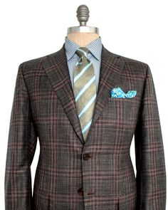 Kiton Olive and Tobacco Plaid Sportcoat 	3 button jacket 	Notch lapel 	Charcoal melton 	Pick stitch detailing 	Front left chest pocket 	Flap pockets 	Fully lined 	Olive lining 	Double vent 	Drop: 7 	55% cashmere, 25% silk, 20% linen 	Handmade in Italy
