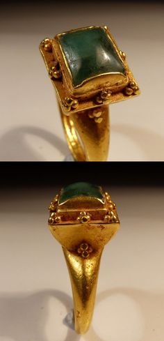 Roman Gold Ring, having a wide shaped band supporting a large 3 tiered square bezel inset with a emerald, surmounted by granular decoration, dating to the 2nd Century AD.