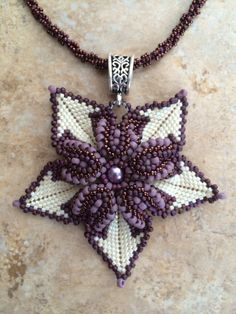 I used peyote stitch to create this handcrafted flower pendant using a variety of different sized glass seed beads in cream, bronze and mauve