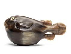 A buffalo-horn netsuke of a fugu fish 19th century Facing ahead as it swims, its tail trailing at the back and its open mouth with inlaid teeth, the eyes of raden with dark horn pupils, unsigned.