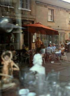 Reflections in a shop window of people eating outside a cafe in Bath Main square