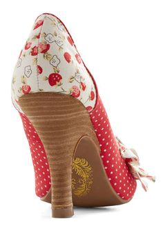 """Searching for the perfect way to describe these delectable, strawberry-printed heels, the only phrase on the tip of your tongue is """"sweet as can be!"""" A stacked heel, a beaded, floral applique, and a darling pattern of white polka dots and yellow flowers make these vintage-inspired red pumps almost too cute for words."""