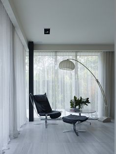 Stepping inside this modern home, a large floor lamp with a white shade provides light above a black upholstered leather chair and a small table. Contemporary Window Treatments, Large Floor Lamp, Kitchen And Bath Design, Street House, Interior Decorating, Interior Design, Australian Homes, Small Tables, Home Renovation